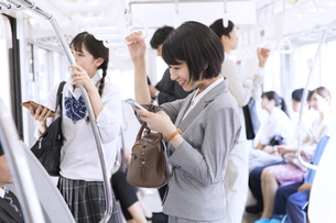 電車でつり革を持ちながらスマホを操作するビジネス女性の写真素材 [FYI02969634]