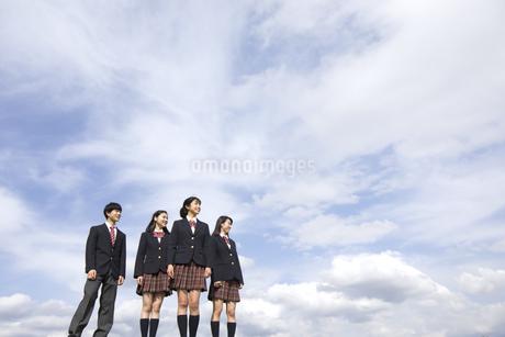 青空をバックに立つ高校生たちの写真素材 [FYI02969635]