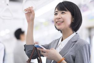 電車でつり革を持ち遠くを見つめるビジネス女性の写真素材 [FYI02969641]
