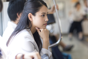 電車の座席に座り遠くを見つめるビジネス女性の写真素材 [FYI02969642]