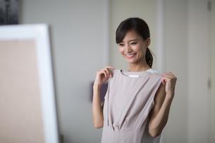 鏡の前で洋服を合わせる女性の写真素材 [FYI02969643]