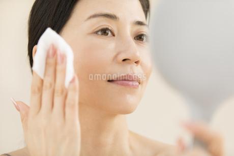 頬にコットンをあてスキンケアをする女性の写真素材 [FYI02969646]