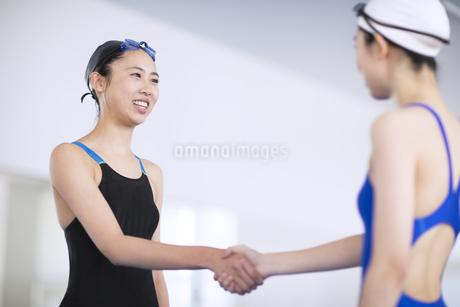握手をする水着の女子学生の写真素材 [FYI02969647]