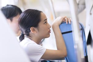 電車の座席に座り遠くを見つめる女性の写真素材 [FYI02969648]