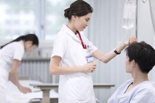 点滴の確認を行う女性看護師の写真素材 [FYI02969653]