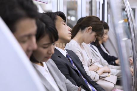 電車で眠るビジネス男性の写真素材 [FYI02969655]