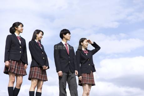 青空をバックに立つ高校生たちの写真素材 [FYI02969661]