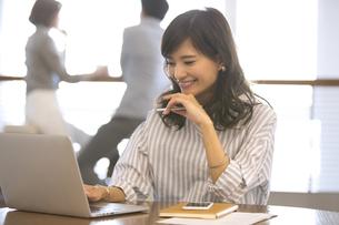 ペンを持ちノートパソコンを見るビジネス女性の写真素材 [FYI02969663]