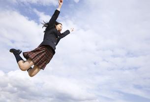 青空をバックにジャンプをする女子高校生の写真素材 [FYI02969667]