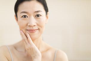頬に片手を添えて微笑む女性の写真素材 [FYI02969668]