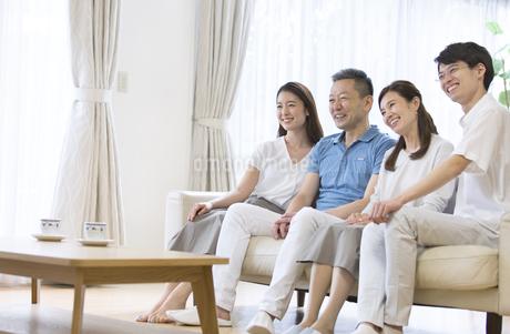 リビングでテレビを見る家族の写真素材 [FYI02969671]