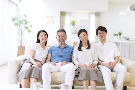 ソファーに座り笑顔の家族の写真素材 [FYI02969676]