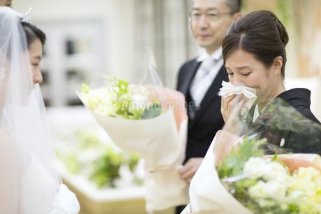 花束を受け取り涙ぐむ母親の写真素材 [FYI02969683]