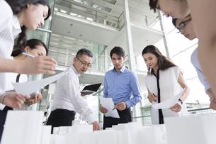 建築模型を使って打ち合せをするビジネス男女の写真素材 [FYI02969684]