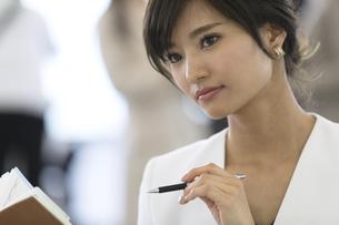 手帳を広げて1点を見つめるビジネス女性の写真素材 [FYI02969692]