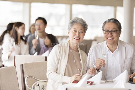 シャンパンを持ち遠くを見るシニア夫婦の写真素材 [FYI02969699]