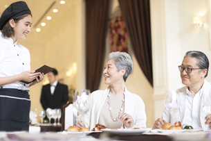 レストランで注文をするシニア夫婦の写真素材 [FYI02969715]