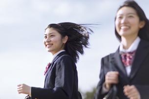 青空をバックに走る女子高校生たちの写真素材 [FYI02969727]