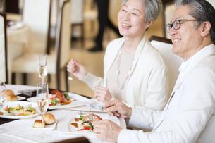 食事をとりながら遠くを見るシニア夫婦の写真素材 [FYI02969729]