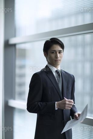 紙とペンを持ちカメラ目線で立つビジネス男性の写真素材 [FYI02969731]