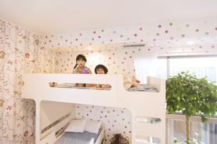 ベッドでカメラ目線の姉妹の写真素材 [FYI02969732]