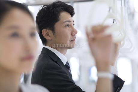 電車でつり革を持ち遠くを見つめるビジネス男性の写真素材 [FYI02969734]