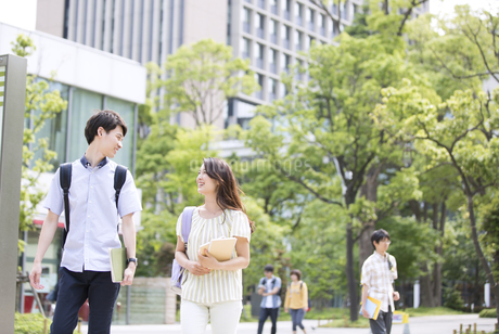 会話をしながら歩く学生の男女の写真素材 [FYI02969738]