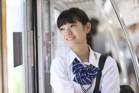 電車で外の景色を見つめる女子高校生の写真素材 [FYI02969739]