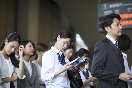 駅のホームで勉強をする女子高校生の写真素材 [FYI02969743]
