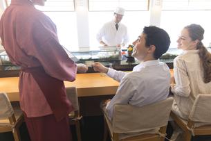 寿司屋で会計をする外国人の男女の写真素材 [FYI02969744]