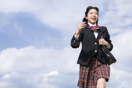 青空をバックに走る女子高校生の写真素材 [FYI02969754]