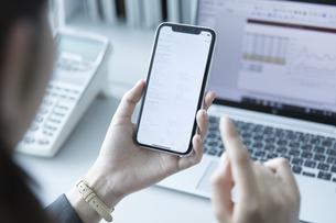 スマートフォンを操作するビジネス女性の手元の写真素材 [FYI02969758]