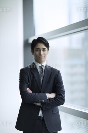 腕を組みカメラ目線で立つビジネス男性の写真素材 [FYI02969760]