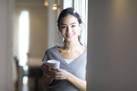 カップを持ちカメラ目線の女性の写真素材 [FYI02969764]