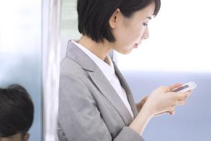 電車でスマホを操作するビジネス女性の写真素材 [FYI02969766]
