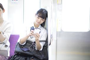 電車で音楽を聴きながらスマホを操作する女子高校生の写真素材 [FYI02969767]