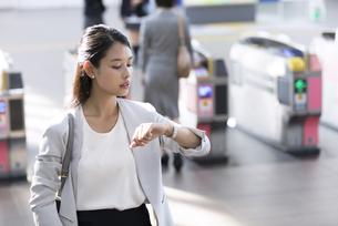 駅の改札付近で時計を見るビジネス女性の写真素材 [FYI02969768]