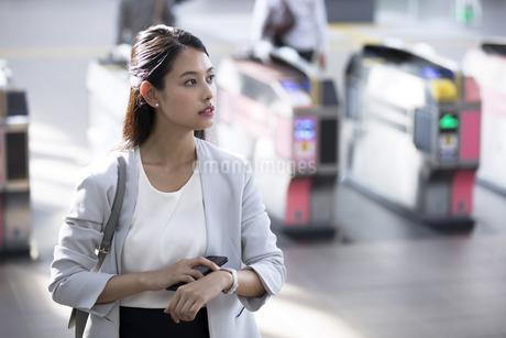 駅の改札付近で時計に触れながら周りを見るビジネス女性の写真素材 [FYI02969769]