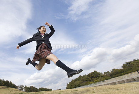 青空をバックにジャンプをする女子高校生の写真素材 [FYI02969770]