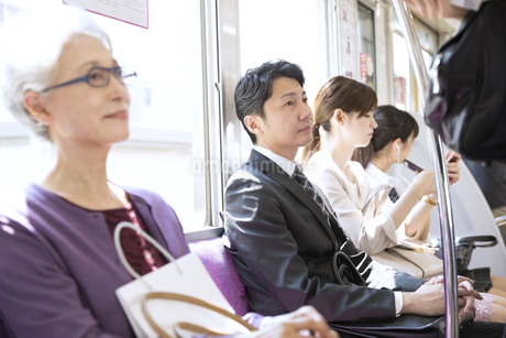 電車の座席に座り遠くを見つめるビジネス男性の写真素材 [FYI02969777]