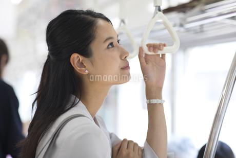 電車のつり革を持ち遠くを見つめるビジネス女性の写真素材 [FYI02969779]