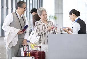 空港カウンターで手続きをするシニア夫婦の写真素材 [FYI02969780]