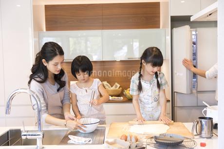 キッチンで料理を作る母親と姉妹の写真素材 [FYI02969782]