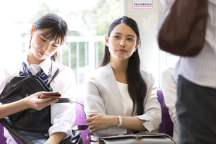 電車の座席に座り遠くを見つめるビジネス女性の写真素材 [FYI02969785]