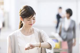 駅の改札付近で時計を見るビジネス女性の写真素材 [FYI02969787]