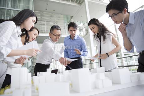 建築模型を使って打ち合せをするビジネス男女の写真素材 [FYI02969791]