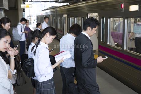 ホームで電車を待つ人々の写真素材 [FYI02969792]