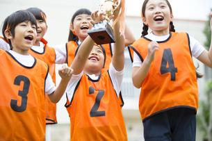 優勝カップを持って喜ぶ子供たちの写真素材 [FYI02969793]