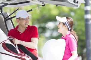 車からゴルフバッグを取り出す夫婦の写真素材 [FYI02969795]