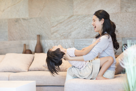 ソファーで戯れる母親と娘の写真素材 [FYI02969801]